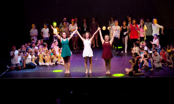 A picture of children of different ages on a stage, performing with three girls at the front of the stage.