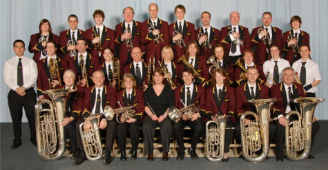 A band holding different brass instruments, sitting down together