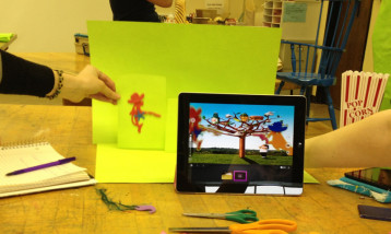 Participants adding animation characters using animation software on a tablet device