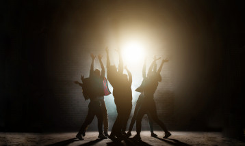 A group of young dancers, back lite on stage