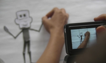 A cartoon figure being drawn while a photo is taken of the figure on a digital camera