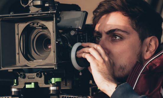 A young man operates a professional camera
