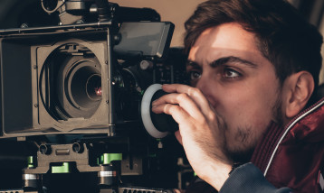 A young man operates a professional camera