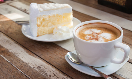 A piece of cake with a hot drink on the side.
