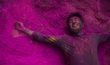 An Indian man lays on the floor covered in pink powder