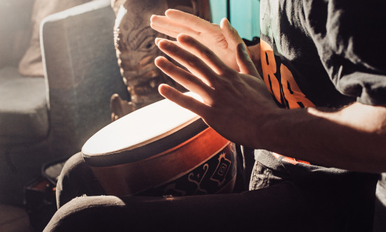 A hand beating on some drums