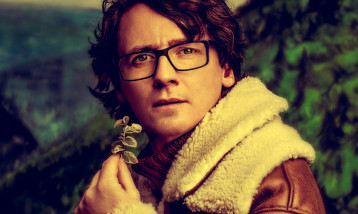 Ed Byrne holds a flower and looks directly at the camera