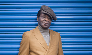 Stephen K Amos stands in front of a blue garage door