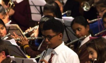 Many children playing different instruments with their music stands in front of them.