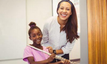 One girl with her flute teacher, both looking happy.