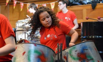 A girl playing steel drums.