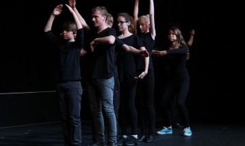 A picture of the Youth Theatre all lined up with different hand movements.