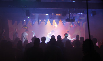 A picture of the 100 studio event , with a band performing on the stage.
