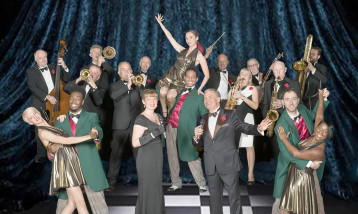 A picture of many dance couples and a band with a few brass instruments on a black and white dance floor.
