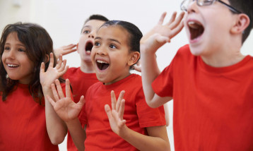 A picture of four children all in red t-shirts having fun at the Summer Music Camp event.