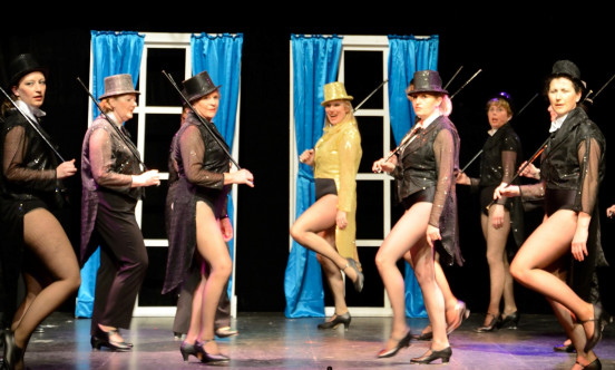 A group of female tap dancers all dressed in black, except one in the middle dressed in yellow.