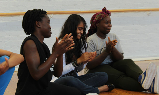 A picture of three young females taking part in the Youth Theatre for 11-16 year old children.