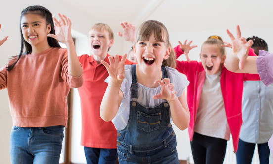 A picture of the 7-11 Youth Theatre club all children acting like monsters with their hands in front of them as claws.