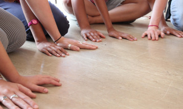 Many people sitting down on the floor with their hands crossing over each other.