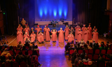 A group of people dressed in pink dresses on a stage in front of an audience.