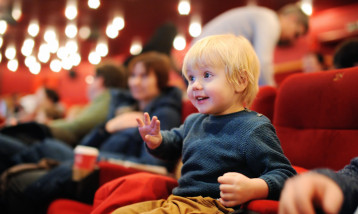 A picture of a toddler on a red seat enjoying a performance.