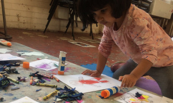 A young girl at a desk colouring in different pictures.