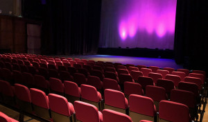 Red seats in the Elliott Hall theatre alongside the stage at the front.