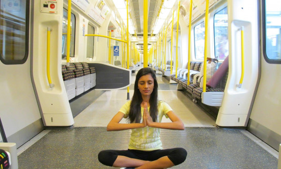 A picture of a female on a train doing yoga.