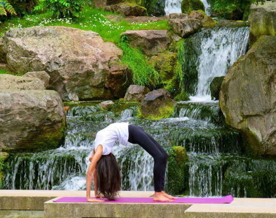 A picture of a female beside waterfalls doing yoga.