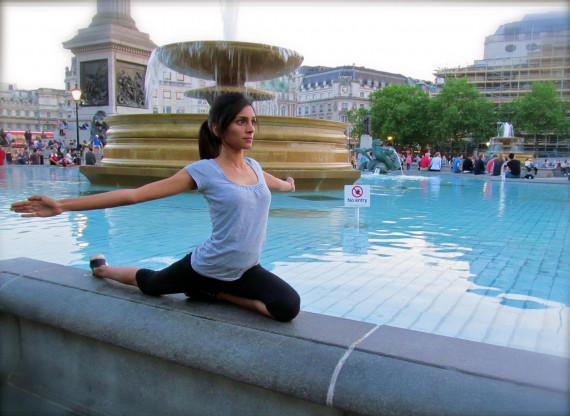 A picture of a female beside a pool of water doing yoga.