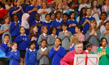 A picture of a choir of small children singing with their hands on their hearts.