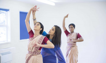 A picture of two females learning Indian dancing and one instructor teaching them.