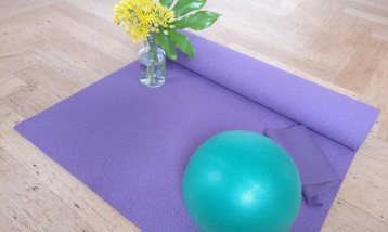 A picture of a pilates mat with a round ball on it and a flower.