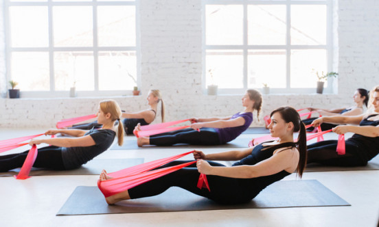 A picture of many women doing pilates on a mat with a pink strap attached  to their feet.