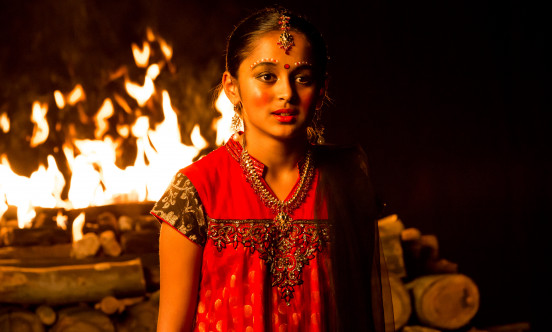 Young girl stands in front of an open fire pit
