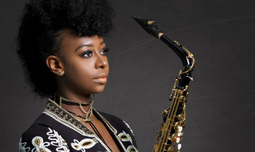 An image of YolnDa Brown holding a saxophone