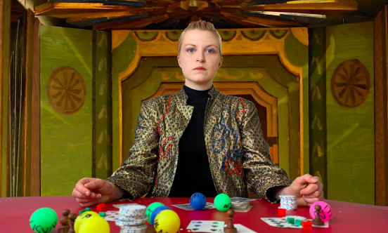 A women sits as a poker table with cards in front of her
