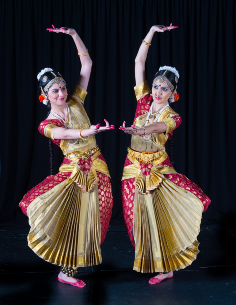 Two women are dressed up in Indian clothing, dancing.