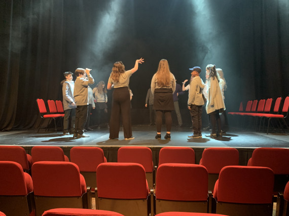 Group of 10 young people in black and grey uniform are gathered in a circle on a black empty stage. Red theatre seats are present in the foreground of the image