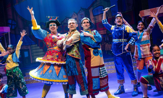 Alladin with panto dame and other cast members on stage in bright costumes